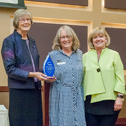Sue Maes, dean of K-State Global Campus, presents the 2016 UPCEA Central Region Engagement Award to Kerri Ebert and Debbie Hagenmaier, Women Managing the Farm committee members, at the K-State Global Campus Honors and Awards Reception in May 2017.